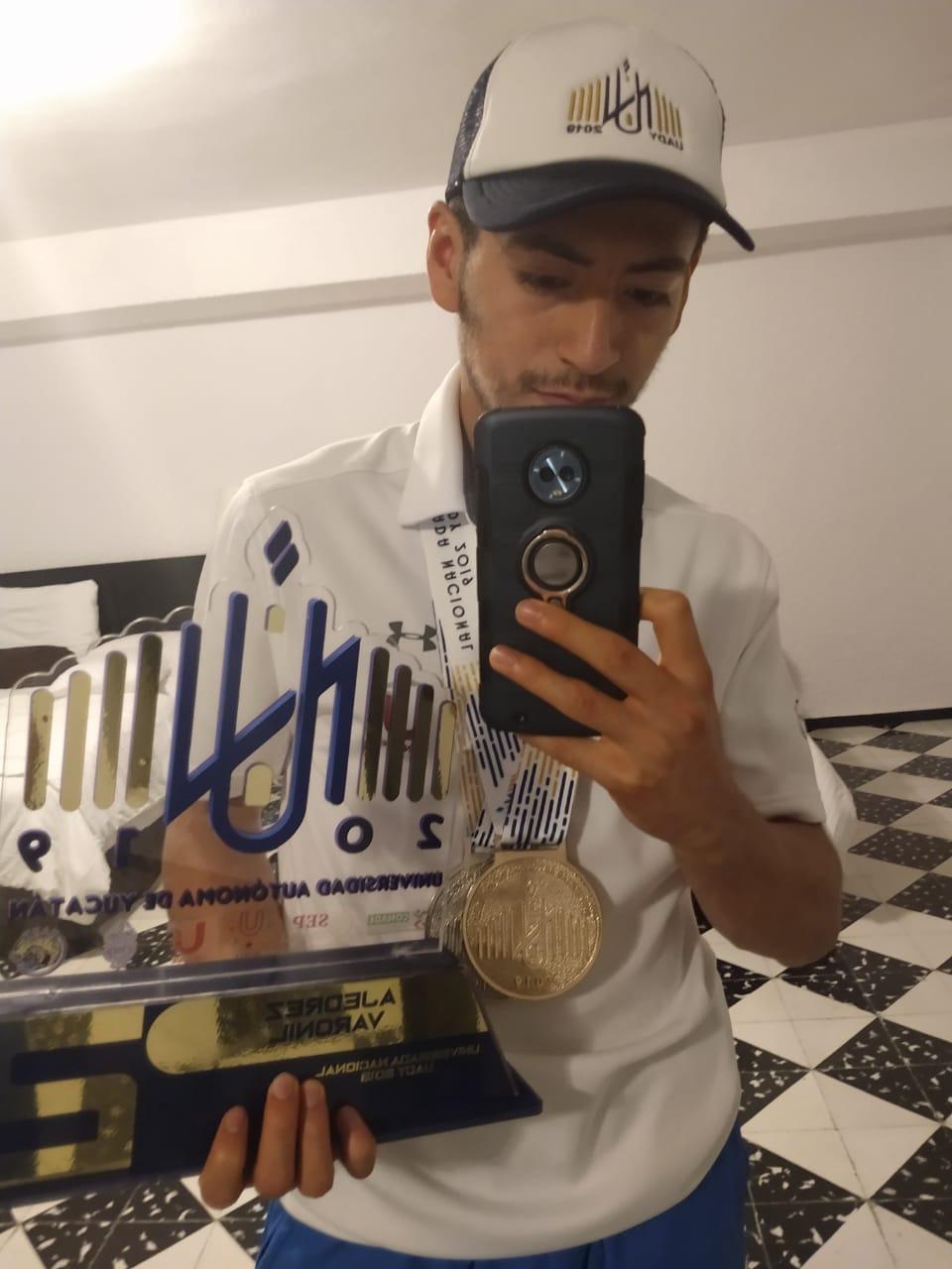 Maestro Fide Isaac Tello, sosteniendo sus tres medallas y el trofeo obtenidos