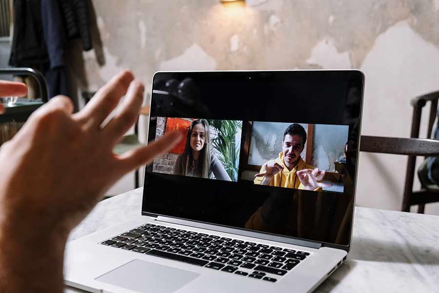 Una persona comunicándose a través de lengua de señas con dos personas a través de una video llamada.