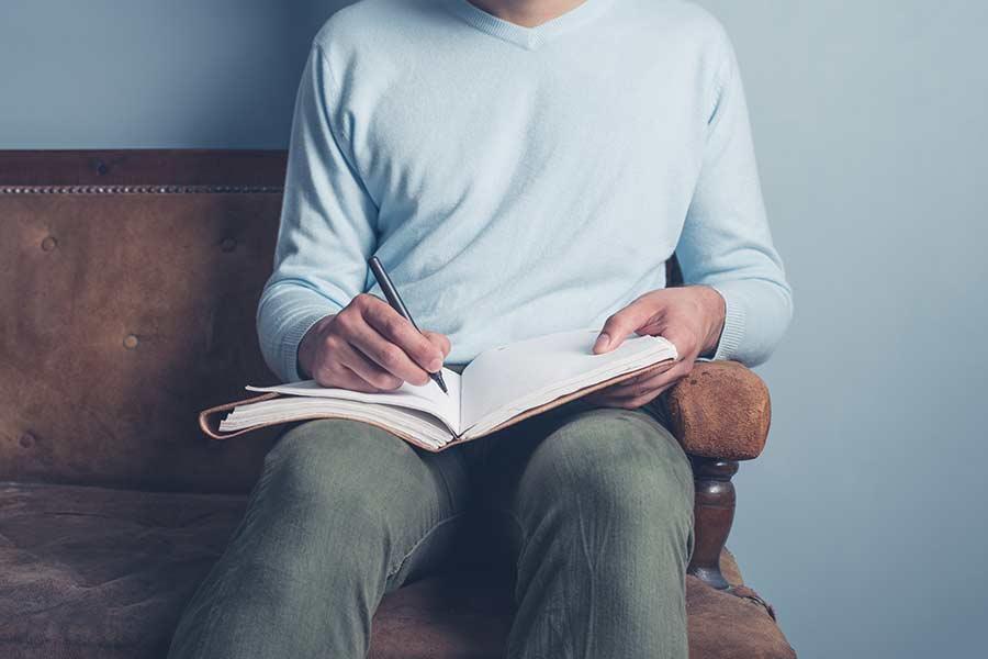 Manos de un chico joven escribiendo un diario