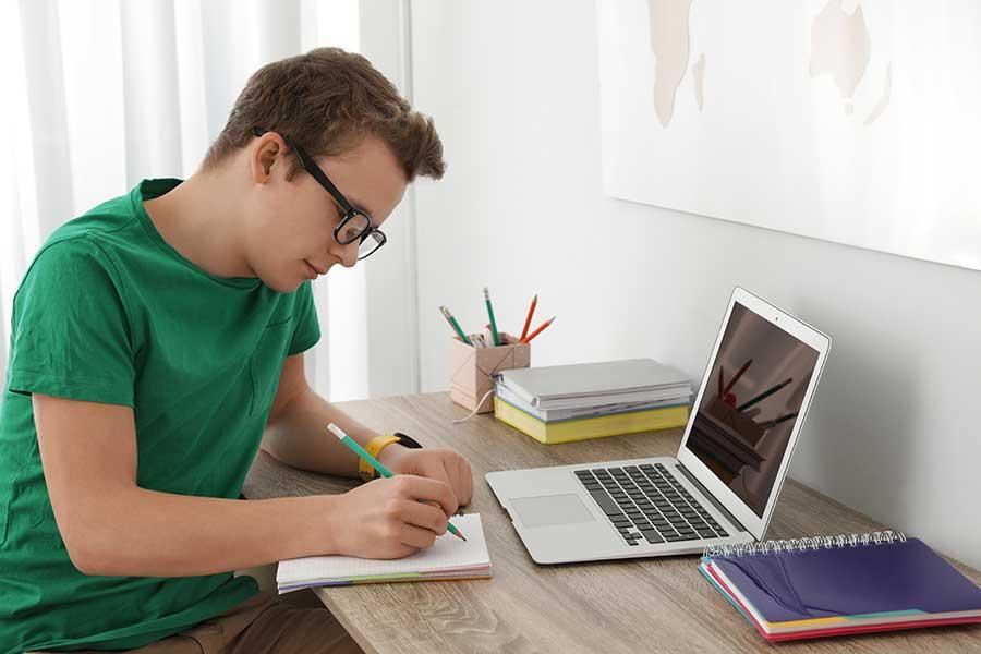 Joven en su escritorio escribiendo sobre una libreta