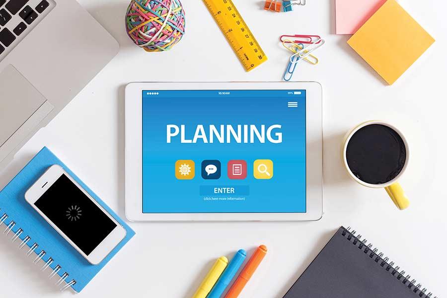 """Tablet con la palabra """"planning"""" y objetos escolares alrededor"""