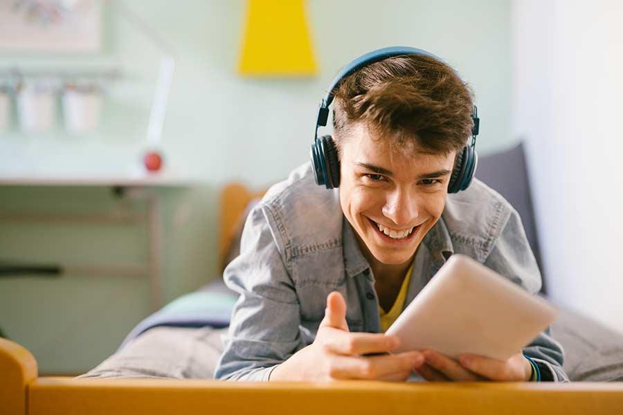 Joven adolescente con audífonos, usando su tablet