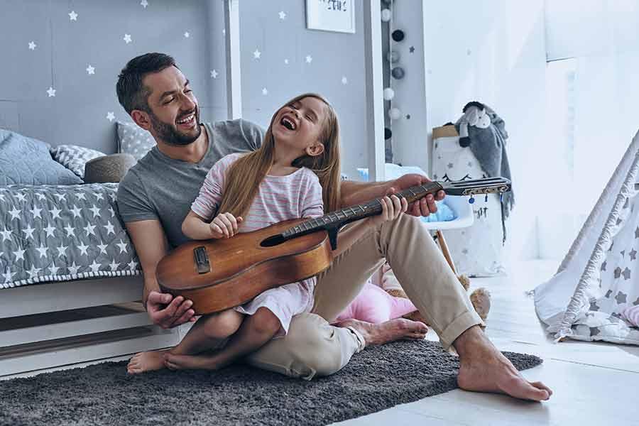 Papá enseñando a su hija a tocar la guitarra